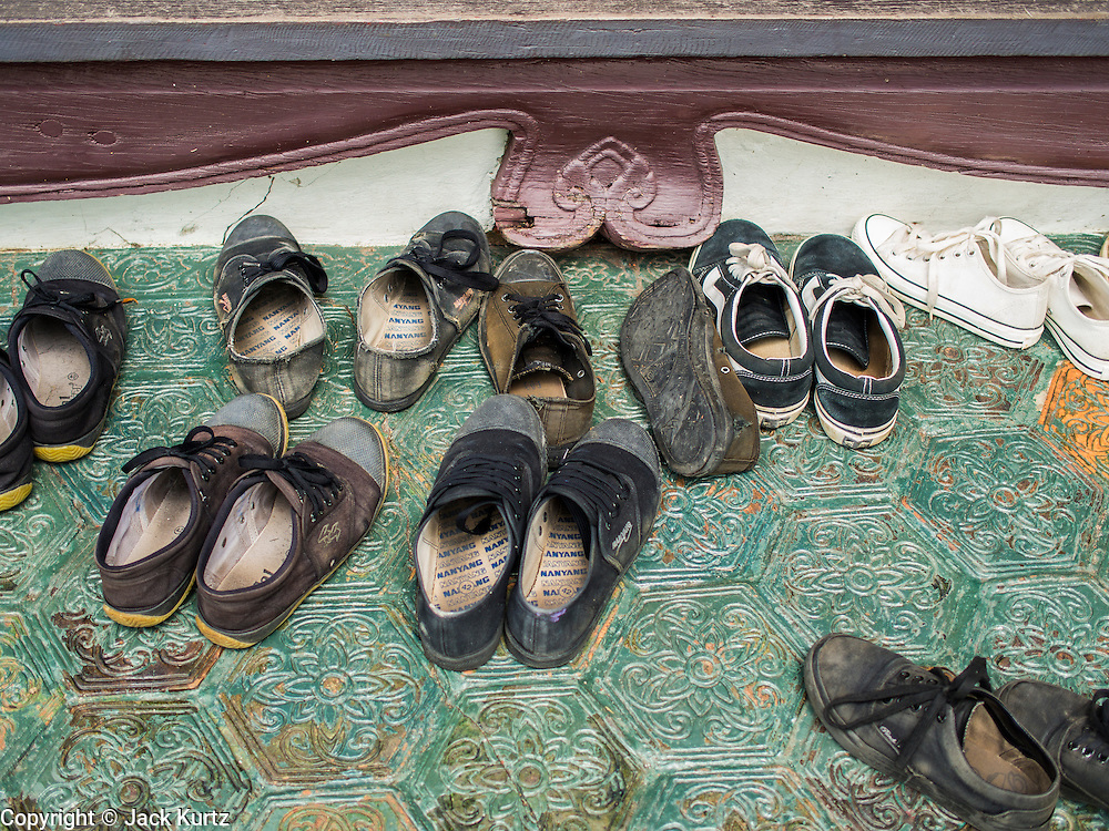 16 JULY 2014 - SAMUT PRAKAN, SAMUT PRAKAN, THAILAND: Children's shoes in the entry of the Phra Kaew Pavilion. It's customary for people to take their shoes off when entering Thai homes and religious buildings. The Phra Kaew Pavilion is a octagonal shaped building at Ancient Siam. It's based on designs common in the Ayutthaya period of Siamese history. Ancient Siam is a historic park about 200 acres (81 hectares) in size in the city of Samut Prakan, province of Samut Prakan, about 90 minutes from Bangkok. It features historic recreations of important Thai landmarks and is shaped roughly like the country of Thailand.      PHOTO BY JACK KURTZ