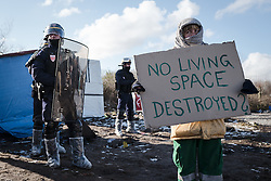 © London News Pictures. Calais, France. 07/03/16. A volunteer stands in silent protest as French riot police enter the 'Jungle' to begin the second week of the demolition. French authorities are evicting and demolishing the southern half of the Calais 'Jungle' camp, which charities estimate to contain 3,500 people. . Photo credit: Rob Pinney/LNP