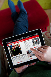 Woman using iPad tablet computer to read online edition of Der Spiegel German current affairs magazine