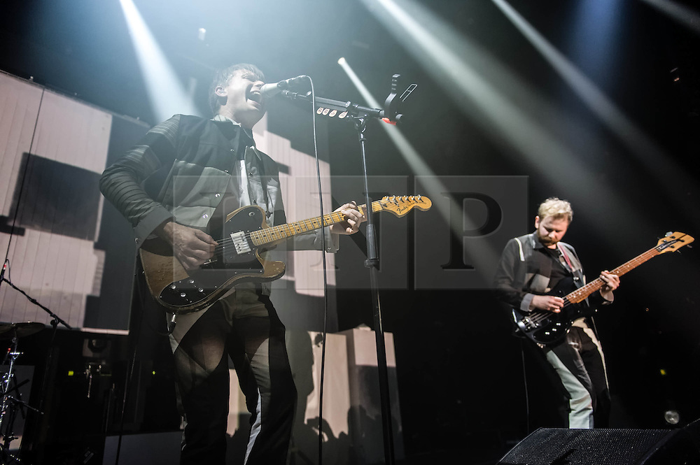 © Licensed to London News Pictures. 14/03/2014. London, UK.   Franz Ferdinand performing live at The Roundhouse.  In this picture - Alex Kapranos (left), Bob Hardy (right).  Franz Ferdinand are a Scottish indie rock band composed of Alex Kapranos (lead vocals and guitar, keyboard), Bob Hardy (bass guitar), Nick McCarthy (rhythm guitar, keyboards and backing vocals), and Paul Thomson (drums, percussion and backing vocals). Photo credit : Richard Isaac/LNP