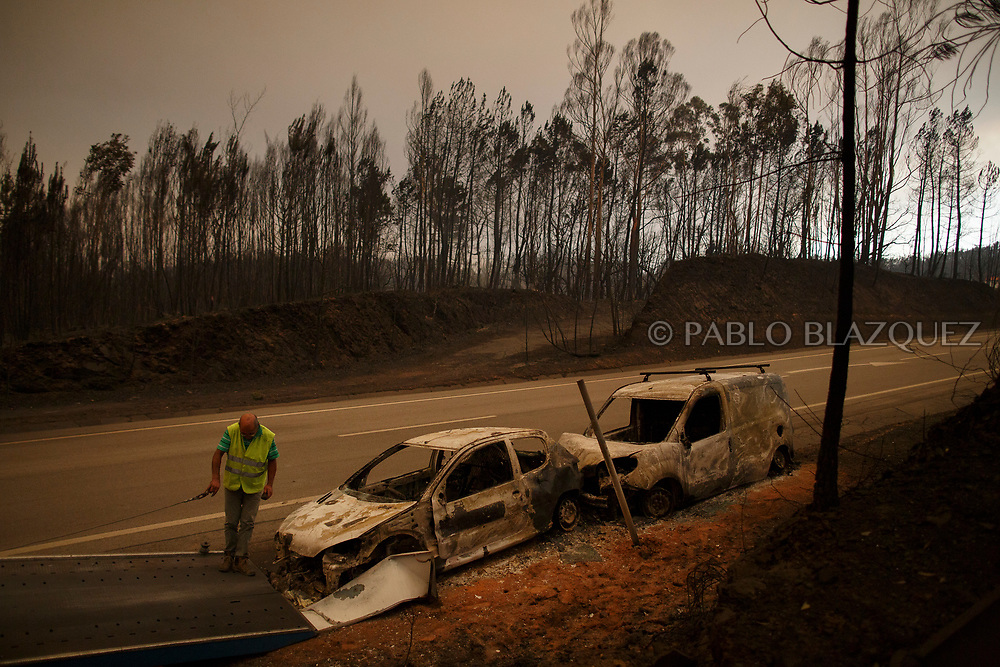 LEIRIA, PORTUGAL - JUNE 18:  A worker picks up a burned car from the road after a wildfire took dozens of lives on June 18, 2017 near Castanheira de Pera, in Leiria district, Portugal. On Saturday night, a forest fire became uncontrollable in the Leiria district, killing at least 62 people and leaving many injured. Some of the victims died inside their cars as they tried to flee the area.  (Photo by Pablo Blazquez Dominguez/Getty Images)
