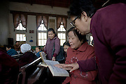 Elderly Chinese women look in a song book as they sing in a Christian church in  Pucheng, Shanxi.