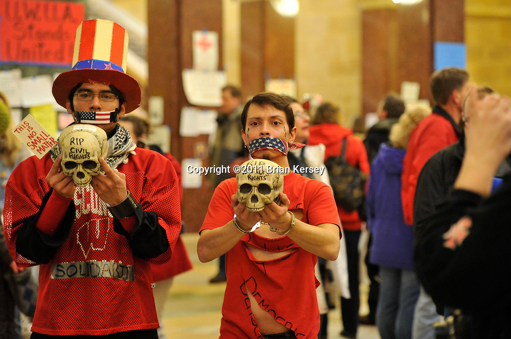 Two silent protesters carry skulls through the state capitol in Madison, Wisconsin on February 23, 2011. The Wisconsin budget proposed by Republican Gov. Scott Walker includes cuts in benefits for state workers and takes away many of their collective bargaining rights.   (Photo by Brian Kersey)