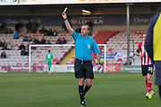 Referee Carl Boyeson shows a yellow card during the EFL Sky Bet League 1 match between Lincoln City and Tranmere Rovers at Sincil Bank, Lincoln, United Kingdom on 14 December 2019.