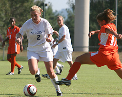 UVA's Jen Redmond dodges a University of Miami defender on October 2, 2005 in Charlottesville, VA.  The Wahoos defeated the Hurricanes 1-0.<br />