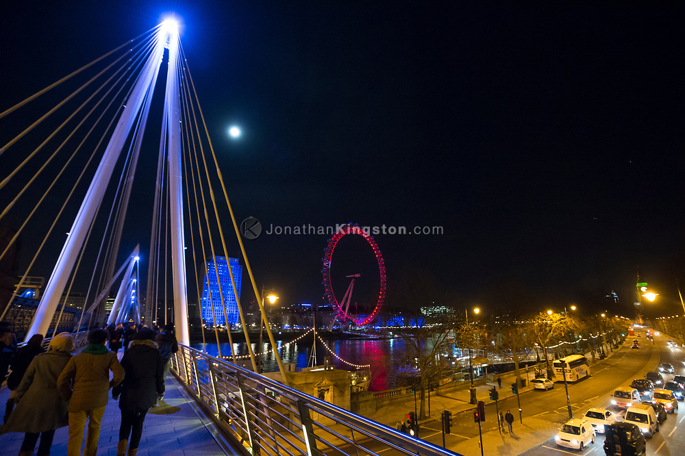 Night view of pedestrians crossing the Golden Jubilee Bridge with the London Eye, illuminated in red, visible in the background in London, England.