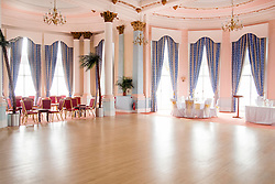 Palm Court Ballrom in the Grand Hotel A Grade II listed building Dominating Scarborough South Bay. When completed in 1867 it was one of the largest hotels in the world, as well as one of the first giant purpose-built hotels in Europe. The hotel is in the shape of a 'V' in honour of Queen Victoria and was designed around the theme of time: <br /> 4 towers to represent the seasons, <br /> 12 floors for the months of the year, <br /> 52 chimneys symbolise the weeks, <br /> originally there were 365 bedrooms - one for each day of the year. <br /> As Scarborough was a famous 'Spa Town' in its heyday the Grand hotels baths included an extra pair of taps so guests could wash in seawater as well as fresh water.<br /> The hotel was badly damaged when the German Navy bombarded the town in 1914.<br /> Three blue plaques outside mark where the novelist Anne Brontë died in 1849, the contribution of the RAF trainees stationed at the hotel during the Second World War, and the original opening of the building.<br />  12 September 2015<br />  Copyright Paul David Drabble<br />  www.pauldaviddrabble.photoshelter.comom