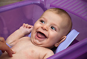 Happy smiling baby being bathed Model released