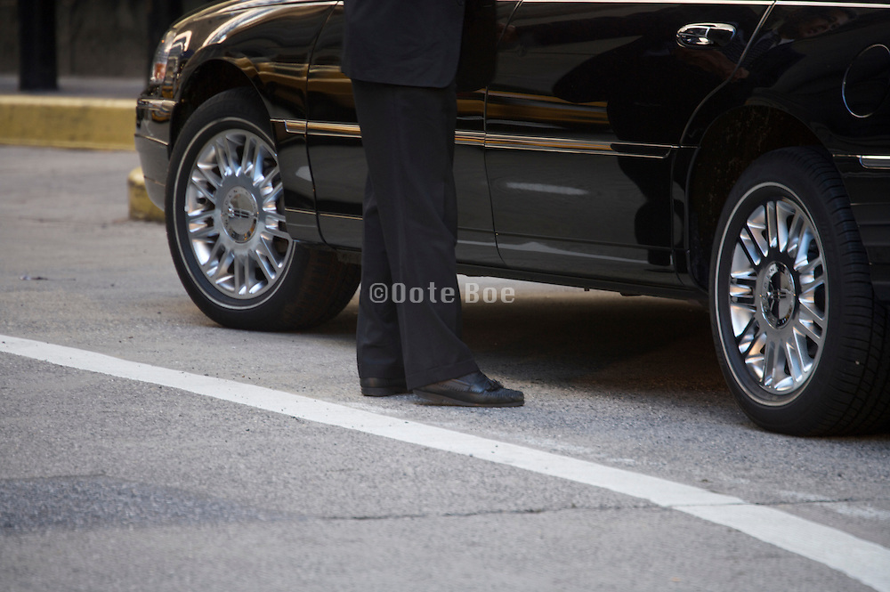 luxury taxi service driver standing by his  limousine