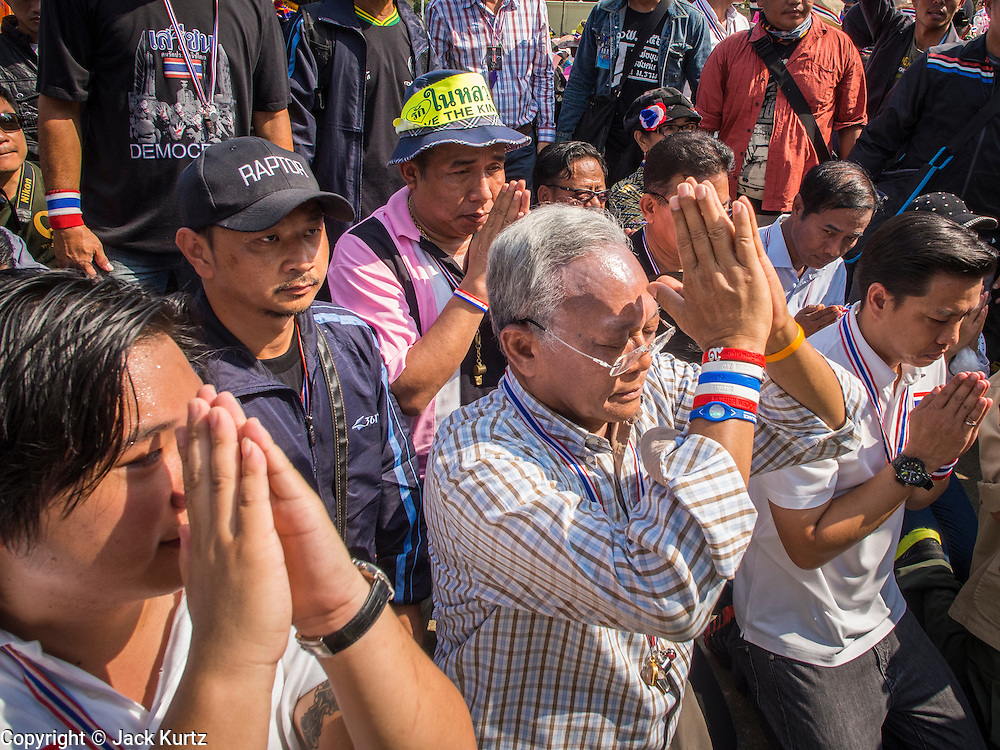 05 JANUARY 2014 - BANGKOK, THAILAND: SUTHEP THAUGSUBAND, leader of the anti-government movement, prays at the statue of King Rama I, the king who founded the current Chakri dynasty, during a stop on a march through Bangkok Sunday. Suthep is a former Deputy Prime Minister and member of the opposition Democrat Party who resigned to organize the protests against the Pheu Thai government.  He led the protestors on a march through the Chinatown district of Bangkok. Tens of thousands of people waving Thai flags and blowing whistles gridlocked what was already one of the most congested parts of the city. The march was intended to be a warm up to their plan by protestors to completely shut down Bangkok starting Jan. 13.     PHOTO BY JACK KURTZ