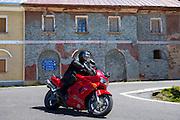 Motorcyclist on Honda VFR drives The Stelvio Pass, Passo dello Stelvio, Stilfser Joch, to Bormio, Northern Italy