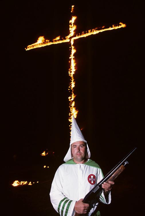 USA, Maryland, Rocky Ridge, Ku Klux Klan member brandishes shotgun at base of burning cross