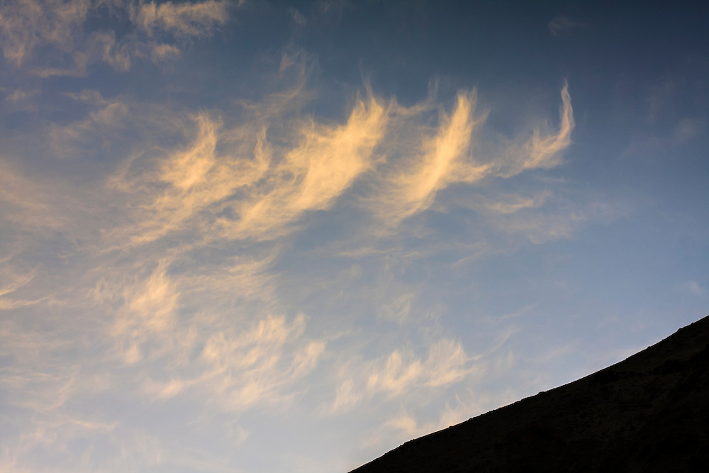 Orange clouds and blue sky at sunset over slope. Hemis National Park. Ladakh. India.