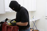 Burglar stealing money from house, close-up