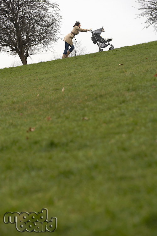 Mother pushing stroller uphill in park