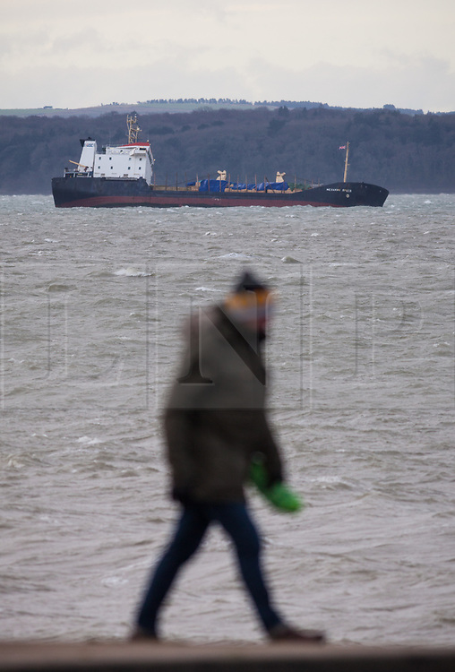 © Licensed to London News Pictures. 27/12/2017. Lee-on-Solent, UK.  A man walking along the promenade at Lee-on-Solent as the stricken Russian cargo vessel, Mekhanic Yartsev, braces the strong winds this morning. The Maritime and Coastguard Agency are formulating a plan to move her to Southampton. 13 crew members were rescued yesterday when the vessel developed a list, so made her way into the sheltered waters of The Solent before the weather conditions deteriorated. Photo credit: Rob Arnold/LNP