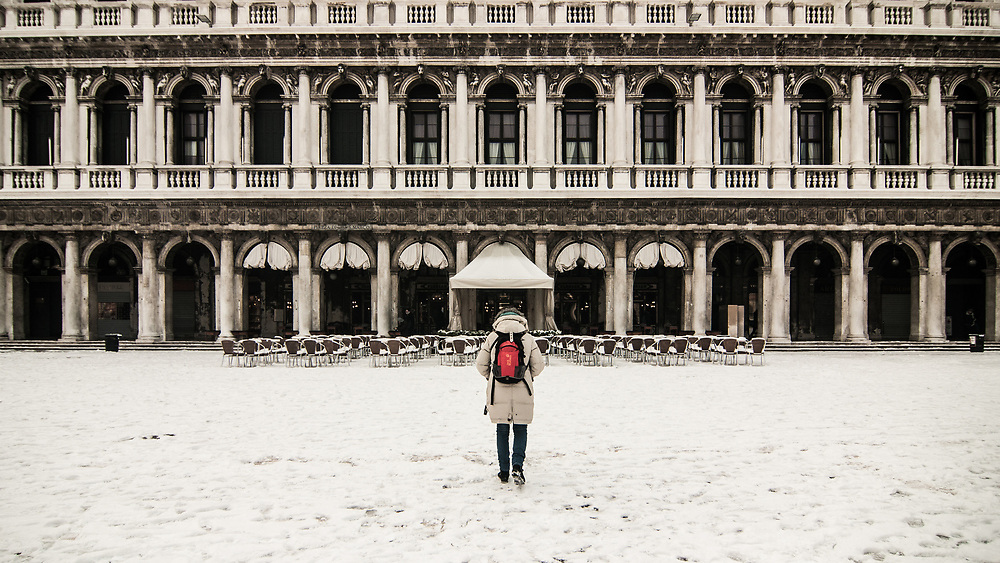 VENICE, ITALY - 28th FEBRUARY/01st MARCH 2018<br /> A woman looks at Procuratie Nuove in Saint Mark square during a snowfall in Venice, Italy. A blast of freezing weather called the &ldquo;Beast from the East&rdquo; has gripped most of Europe in the middle of winter of 2018, and in Venice A snowfall has covered the city with white, making it fascinating and poetic for citizen and tourists.   &copy; Simone Padovani / Awakening