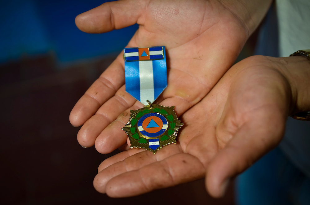 "Marcos Menjivar, 20, displays his medal at Canton El Zapotal school in Chalatenango, El Salvador. In 2010, when he was 18 years old, Menjivar was part of a group of students, trained in disaster response by the international ngo, Plan UK, that took charge of rescuing 80 elderly and mobility impaired residents of his community when a mudslide destroyed their homes.  For his efforts, he was awarded this medal from the National Civilian Protection Commission.  When asked how he felt when his heroism was rewarded, he said: ""In the beginning we were completely surprised because we never thought we would be rewarded for doing something that we thought it was our duty to do. We never expected to get any type of recognition. We did it to help people, to help our community."""