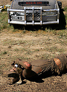 """A festival-goer takes a sip of his drink while laying in the mud at the annual Deniliquin Ute Muster in Deniliquin, Australia. A """"ute"""" is a term used in Australia for a utility vehicle, popular in the rural areas and used for farming and other work needs."""