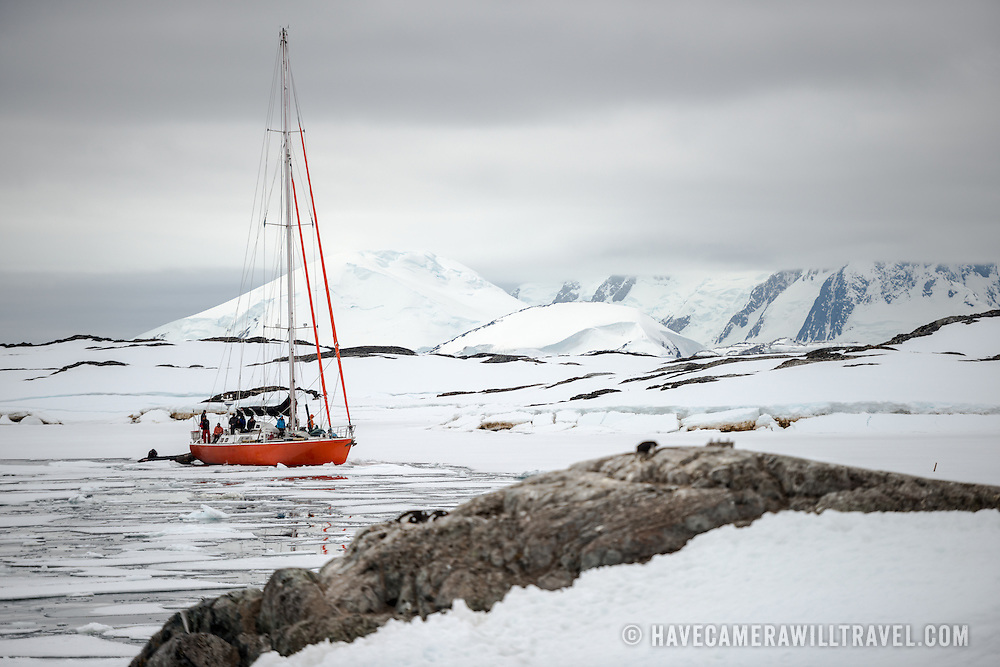 A sailboat moves carefully through the sheets of sea ice near Galindez Island on the Antarctic Peninsula.