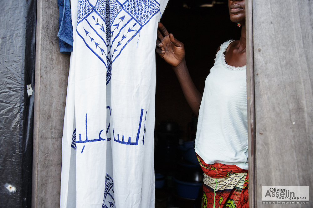 Aminata Nombre, 34, who is HIV positive, stands in the doorway of her home in the Campement neighborhood of Abidjan, Cote d'Ivoire on Wednesday July 10, 2013. Aminata is under ARV treatment and takes three pills every day.