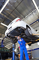 Technician working on car at automobile repair shop