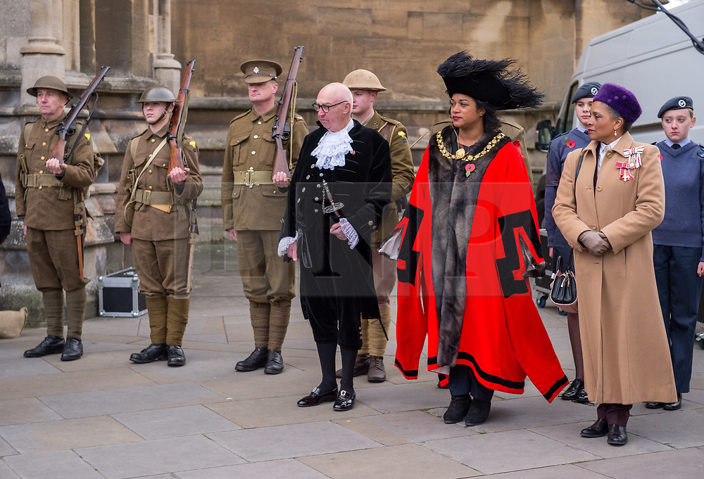 """© Licensed to London News Pictures. 27/10/2018. Bristol, UK. The Royal British Legion launch this year's Bristol Poppy Appeal, """"One thousand poppies, for one hundred years, for one million lives"""" at Bristol Cathedral. For the launch of the 2018 Bristol Poppy Appeal at 11am on 27 October, the Royal British Legion recreated a scene from the end of WW1 outside Bristol Cathedral on College Green, and Colonel Clive Fletcher-Wood read the war poem In Flanders Fields. They were joined by Civic Dignitaries pictured left-right, City of Bristol High Sheriff Mr ROGER OPIE, Bristol's Lord Mayor CLEO LAKE and the Lord Lieutenant of Bristol PEACHES GOLDING. A Bugler and the Bristol Military Wives Choir performed songs from their new album 'Remember'. Staff at MOD Filton filled 400 sandbags with eight tonnes of sand to build trenches and recreate 'Flanders Fields' and planted over 1000 waterproof poppies on College Green. Poppies and sandbags can be sponsored by individuals wanting to remember those who fought and died in conflict. There were re-enactors in WW1 uniform from Somerset Light Infantry (known as the West Country Tommys), as well as medics and nurses with equipment from the time. Bristol's own 'War Horse' (Buzz from Blagdon Horsedrawn Carriages) was on College Green behind the improvised barbed wire to represent the 350,000 horses that left Avonmouth for the frontline during WW1. There are also 10,000 knitted poppies on display both in and outside Bristol Cathedral following 'The Charfield Yarn Bombers' incitement to locals to get knitting to mark the occasion, with a display inside the Cathedral organised by Helen Date. Photo credit: Simon Chapman/LNP"""