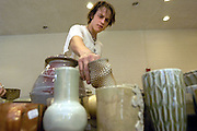 16194Siegfried Hall Pottery Sale..Luke James, a sculpture student from Athens, looks at pottery at the Siegfried hall Pottery sale..Hanson Photo
