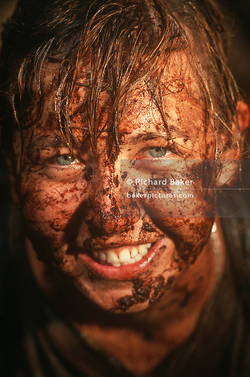A young girl volunteer is caked in mud after an activity on a Raleigh International expedition in the rainforests of Brunei, Borneo. Beaming from ear to ear, the lady relishes her time here in one of the remotest and most dangerous habitats on the planet. It will have been a life-changing experience for her and her new-found friends from all over the world who will have had to raise several thousands of sponsored Pounds for the privilege of spending two months away from a dull, comfortable life at home, rather than building community projects like bridges or schools. Raleigh International is a charity that provides adventurous and challenging expeditions for people from all backgrounds, nationalities and ages, especially young people. Over the last 23 years, 30,000 people have been involved in more than 250 expeditions to over 40 countries.