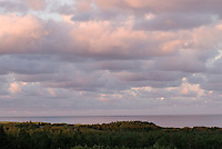 The sunset colors the clouds and ocean at Basin Head beach, Prince Edward Island, Canada.