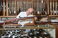 Mature gun shop owner looking at rifle in store