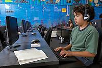 School boy wearing headphones in computer room