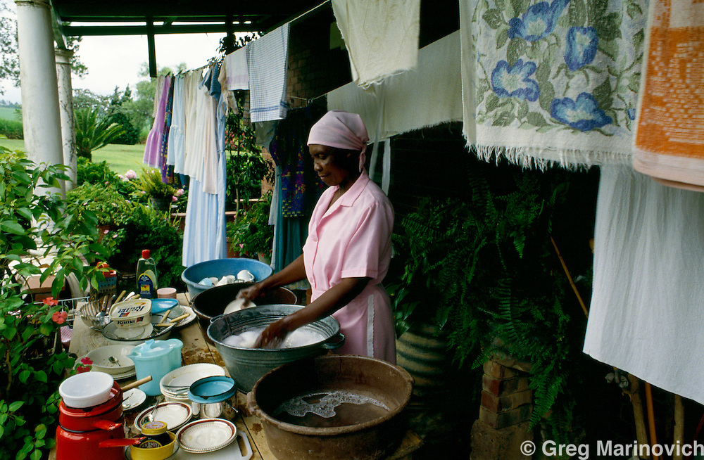 A domestic workers cleans dishes outside a white families home in Wartburg, KwaZulu Natal, South Africa. 1993.