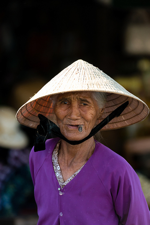 Elderly Vietnamese woman wearing a conical hat at her market stall in Hue