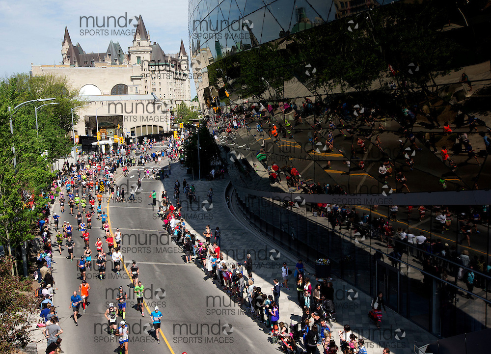 (Ottawa, Canada---25 May 2015) Runners go past the convention centre and away from the Chateau Laurier during the marathon during the Tamarack Run Ottawa Race Weekend.