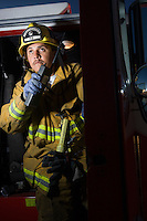 Firefighter using walkie talkie by fire engine
