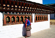 A native woman saying prayers and using a prayer wheel at Tashichho Dzong in Thimpu