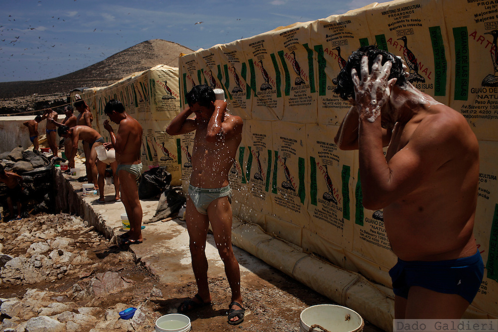 Miners take a bath after a 8 hour shift mining, sieving, packing and shipping guano in the Ballestas islands  in Peru, Oct. 9, 2011. Along the dry and magnificent Peruvian Pacific coast, 22 scattered islands are home to millions of migratory birds such as guanays, boobies and pelicans..Nesting in these  island for millennia their excreta has been used by ancient civilizations to fertilize Andean crops and sustain evolved societies. Now, being one of the finest organic fertilizers in the world they move an economy of around 10 billion dollars, considering the average price of 500 USD a ton, according to  Rural Agrarian Productive Development Program (Agrorural) .The bird dung, also known as guano, reached its greatest economic importance in the 19th century as a coveted resource being exported to the United States, England and France..But now  the country, being led by a leftist president, hopes to benefit mostly small farmers by boosting organic agriculture through these natural fertilizers.. (Photo Dado Galdieri)