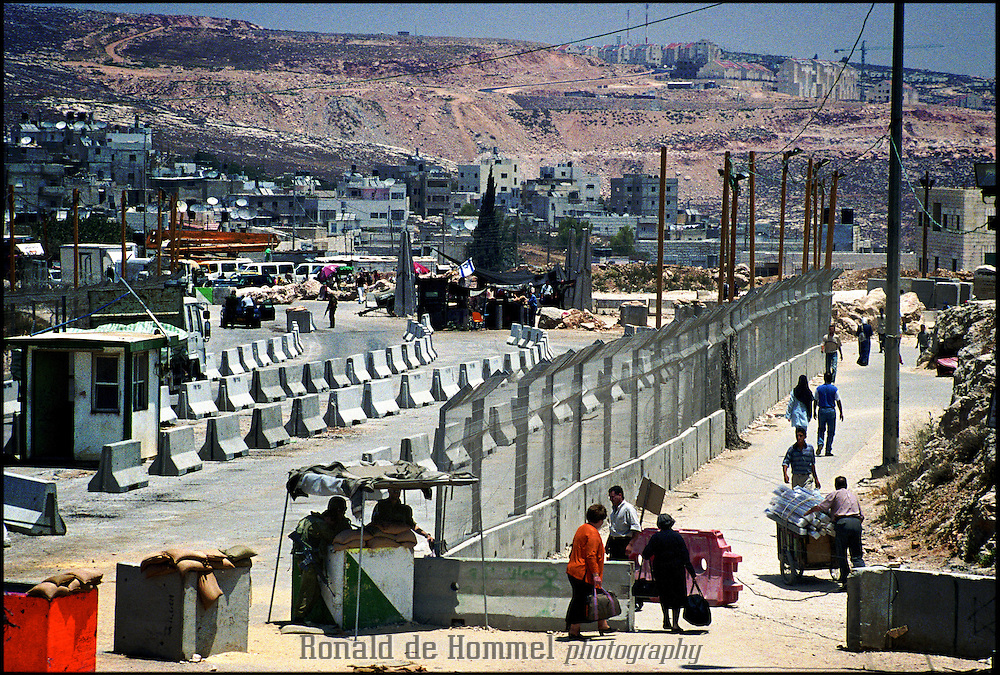 2002-06-12 Ramallah, Palestinian Territories. Checkpoint Kalandia. The most notorious checkpoint between Israel and the occupied territories. Most trafic between Jerusalem and Ramallah has to go through here. Palestinians often have to wait for hours in the sun or rain to be checked. Many times the post is closed without a reason.