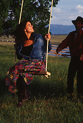 Woman being pushed on a rope swing by a man on a ranch in New Mexico