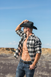 cowboy with open shirt outdoors