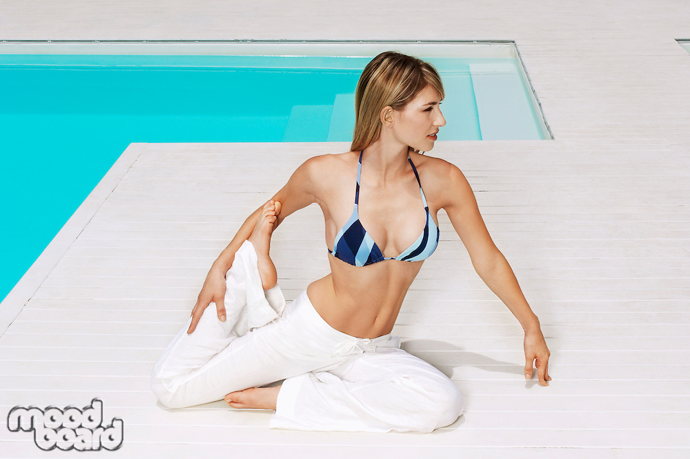 Young woman stretching legs by swimming pool front view full length