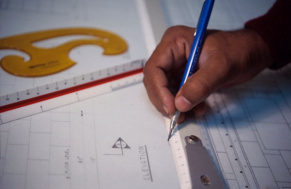 Stock photo of a person using a t-square to draw up plans on a drafting table