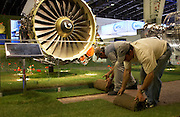 Rolls of turf are rolled up by exhibition workers at the end of a long day at the Paris Air Show, Le Bourget France. Removing the real grass from at the CFM stand (a company formed from SNECMA and General Electric jet engines) that manufactures a family of 7,200 commercial and military jet engines for Airbus and Boeing airliners. The men bend over to make a tight roll of organic lawn to keep it fresh and watered overnight before another hot day in this hall. Alongside them, a giant turbofan engine is seen, its huge turbine blades lit by artificial lights. The Paris Air Show is a commercial air show, organised by the French aerospace industry whose purpose is to demonstrate military and civilian aircraft to potential customers.
