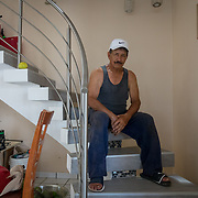 SEPTEMBER 25 - CANOVANAS, PUERTO RICO - <br /> Jose Torres's sits on the stairs to the 2nd floor of his San Isidro neighborhood home. During the path of Hurricane Maria, Torres, a boxing instructor, kept positioning the gas jugs behind him as the water rose inside his house. He is a diabetic and lost all his medications when his two story house was flooded up to seven feet. <br /> (Photo by Angel Valentin for NPR)