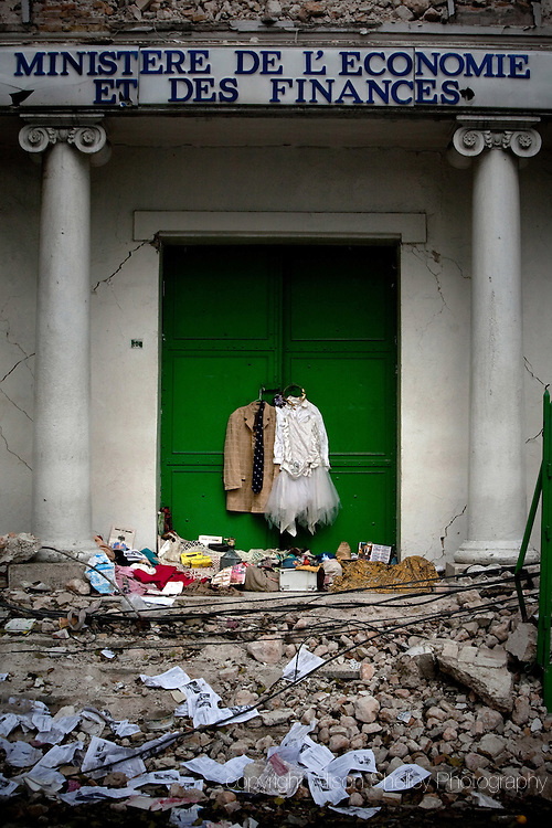 A men's suit coat and women's white dress hang on the front door to the destroyed Ministry of Economy and Finance in downtown Port au Prince, Haiti, Friday, February 26, 2010.