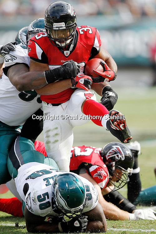 Atlanta Falcons running back Michael Turner (33) runs though tacklers for a second quarter first down during the NFL week 6 football game against the Philadelphia Eagles on Sunday, October 17, 2010 in Philadelphia, Pennsylvania. The Eagles won the game 31-17. (©Paul Anthony Spinelli)