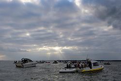 © Licensed to London News Pictures. 18/09/2016. Portsmouth, UK. Players make their way to the match on a boat. Teams take part in the  Bramble Bank Cricket Match in the middle of The Solent strait on September 18, 2016. The annual cricket match between the Royal Southern Yacht Club and The Island Sailing Club, takes place on a sandbank which appears for 30 minutes at lowest tide. The game lasts until the tide returns. Photo credit: Ben Cawthra/LNP