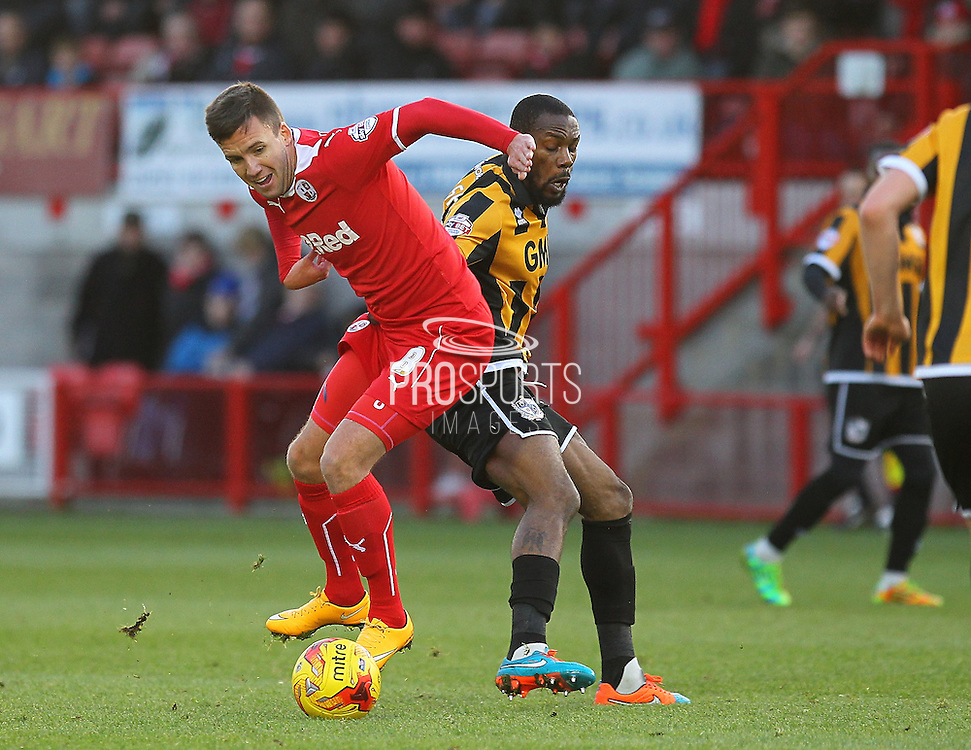 Crawley's Jimmy Smith battles with Port Vale's Danny N'Guessan during the Sky Bet League 1 match between Crawley Town and Port Vale at Broadfield Stadium, Crawley, England on 20 December 2014. Photo by Phil Duncan.