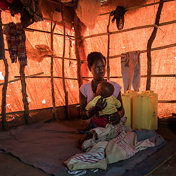 Mary, 17, holds her 6-month-old baby Emmanuel at her tent in the Bidi Bidi refugee settlement in north Uganda. <br /> Mary, a refugee from South Sudan, arrived to Bidi Bidi in August 2016. <br /> Mary was married at 15 and she doesn't know where her husband is. She fears he has died during the conflict in South Sudan.